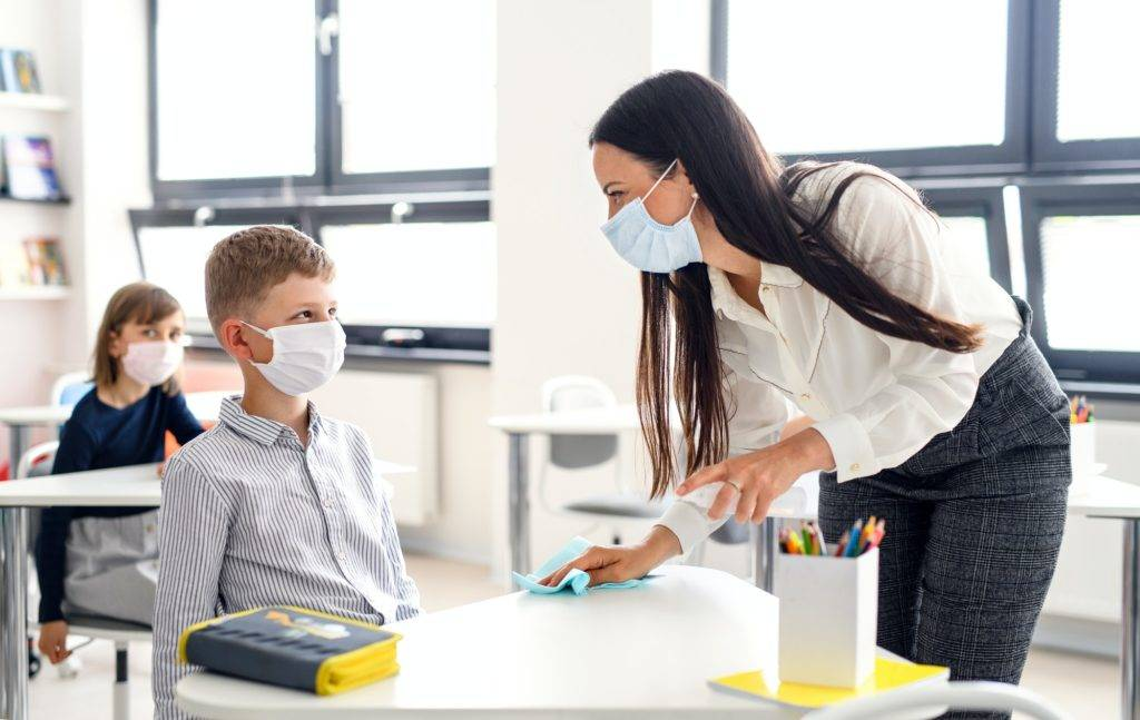 Teacher and children with face mask back at school, disinfecting desks